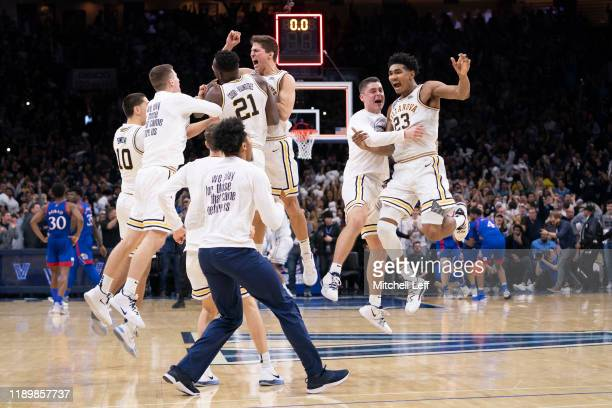 Cole Swider, Dhamir Cosby-Roundtree, Collin Gillespie, and Jermaine Samuels of the Villanova Wildcats celebrate with their teammates after defeating...
