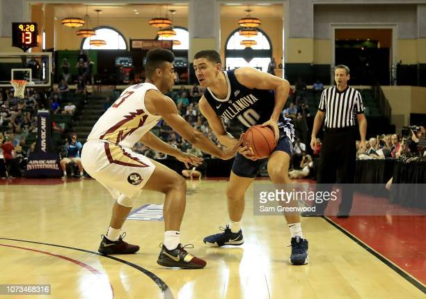 Cole Swider of the Villanova Wildcats is defended by Anthony Polite of the Florida State Seminoles during the game at HP Field House on November 25...
