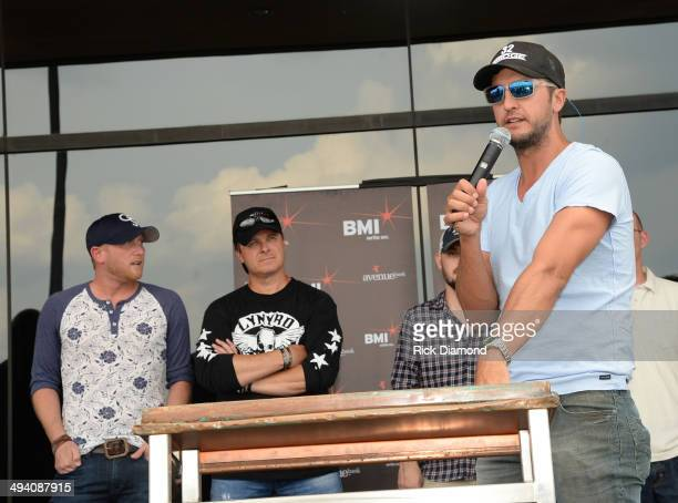 Cole Swindell and cowriter Shane Minor are congradulated by Luke Bryan as he helps Celebrate Cole Swindell's First No1 Song 'Chillin' It' at BMI...