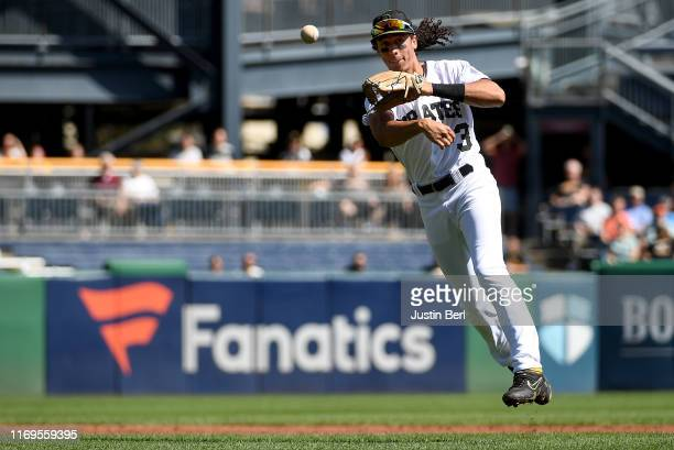 Cole Tucker of the Pittsburgh Pirates makes a throwing error as he attempts to force out Donnie Walton of the Seattle Mariners at first base in the...