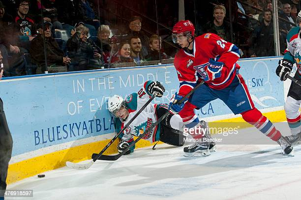 Cole Wedman of the Spokane Chiefs checks Nick Merkley of the Kelowna Rockets into the boards during third period on March 5, 2014 at Prospera Place...