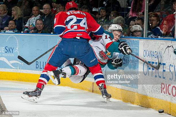 Cole Wedman of the Spokane Chiefs checks Rourke Chartier of the Kelowna Rockets into the boards behind the net during first period on March 5, 2014...