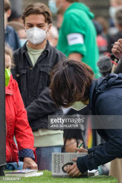 Co-leader of Germany's Greens Buendnis 90/Die Gruenen and the party's candidate for Chancellor Annalena Baerbock signs a copy of her book at an...