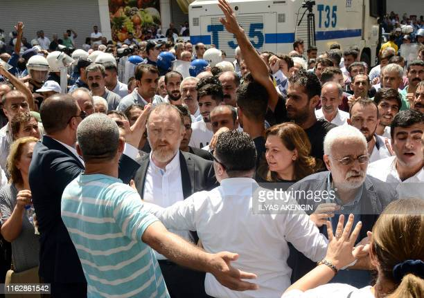 Co-leader of pro-Kurdish Peoples' Democratic Party Sezai Temelli and supporters, surrounded by Turkish anti riot police officers, attend a protest...