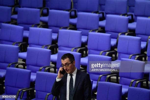 Coleader of the Greens Cem Oezdemir makes a phone call as he waits for the opening of a parliamentary session at the Bundestag in Berlin on January...