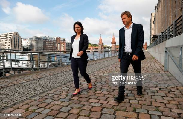 Co-leaders of Germany's Green party Annalena Baerbock and Robert Habeck walk along the river Spree as they arrive for a closed meeting with the...