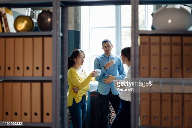 coleagues chatting and drinking coffee in office kitchenet - rumor stock pictures, royalty-free photos & images
