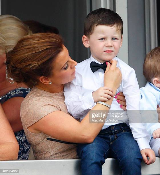 Coleen Rooney adjusts son Kai Rooney's bow tie as they watch the racing as they attend the Crabbie's Grand National horse racing meet at Aintree...