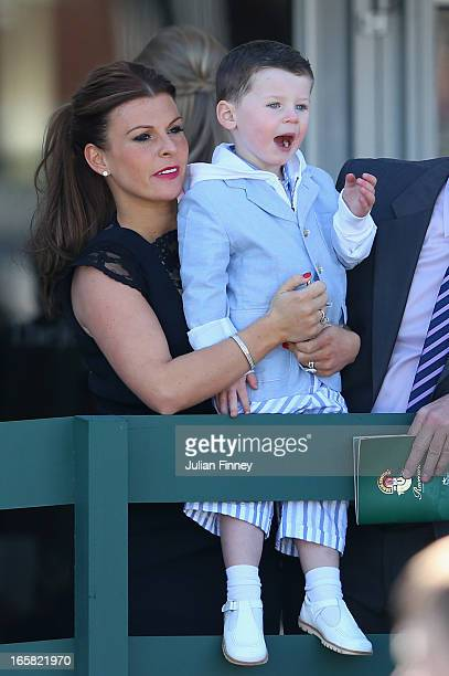 Coleen Rooney and her son Kai Rooney watch on during the John Smiths Grand National at Aintree Racecourse on April 6 2013 in Liverpool England
