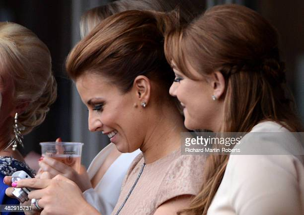 Coleen Rooney looks at a photo on her camera during Day 3 Grand National day of the Aintree races at Aintree Racecourse on April 5 2014 in Liverpool...