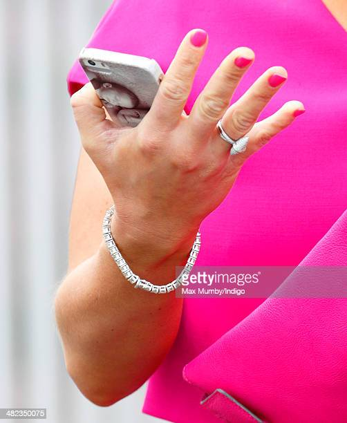 Coleen Rooney uses her iPhone as she attends day 1 of the Crabbie's Grand National horse racing meet at Aintree Racecourse on April 3 2014 in...