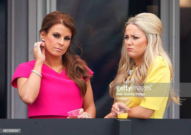 Coleen Rooney watches the racing as she attends day 1 of the Crabbie's Grand National horse racing meet at Aintree Racecourse on April 3 2014 in...