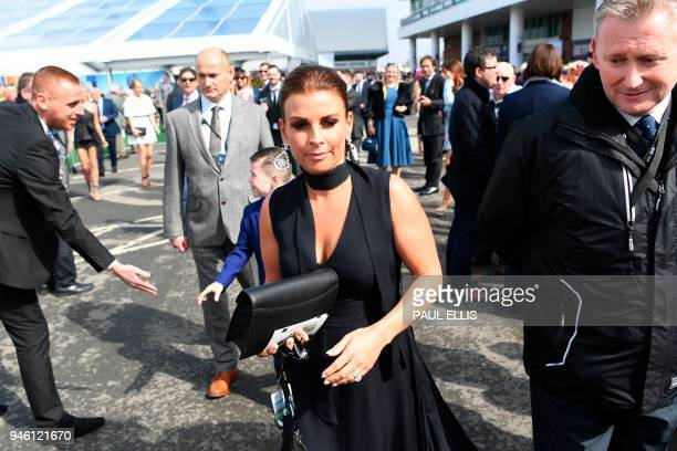 Coleen Rooney wife of Everton's football player Wayne Rooney arrives to attend the final day of the Grand National Festival horse race meeting at...