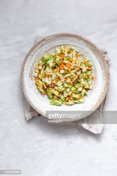 coleslaw of cabbage, carrots and various herbs with mayonnaise in a large plate on a marble background with copy space - raw food diet stock pictures, royalty-free photos & images