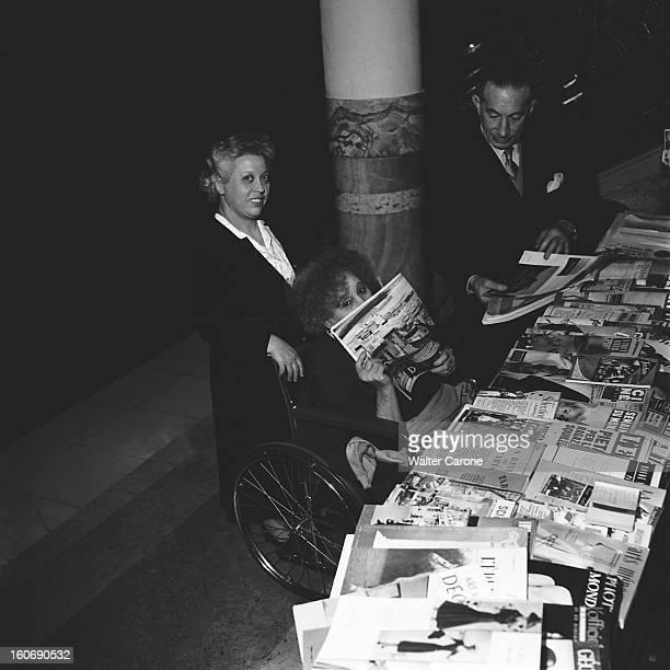 Colette COLETTE assise dans son fauteuil roulant lisant un magazine devant un étalage de revues et journaux divers