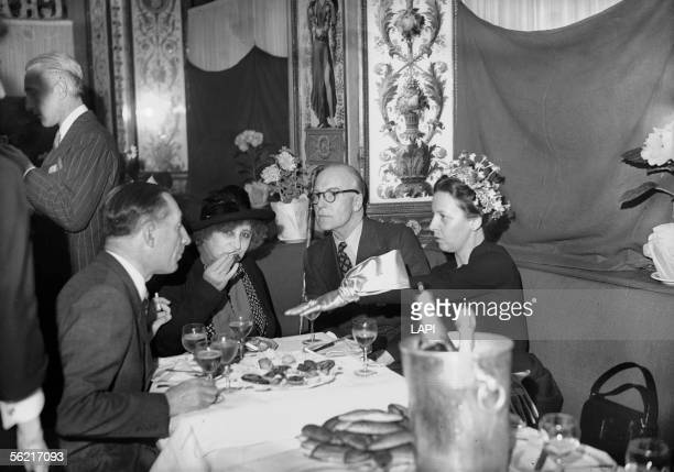 Colette French writer and her husband Maurice Goudeket on the left during a cocktail organized by the decorator Christian Berard Paris restaurant of...