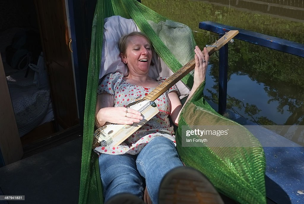 Colette Sloam from Otley relaxes in a hammock and plays her guitar as she visits the Skipton Waterway Festival on May 3, 2014 in Skipton, England. The Waterway festival is a three day annual canal boat event held on the Leeds and Liverpool canal. The event brings together boaters and the local community who take part in the festival activities.