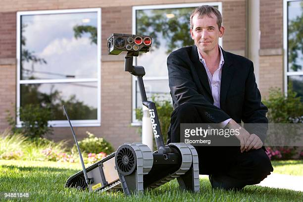 Colin Angle, chief executive officer of iRobot Corp., poses with an iRobot Small Unmanned Ground Vehicle at the company's new headquarters in...
