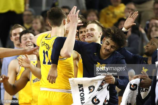 Colin Castleton of the Michigan Wolverines celebrates with teammates on the bench while playing the Nebraska Cornhuskers at Crisler Arena on February...