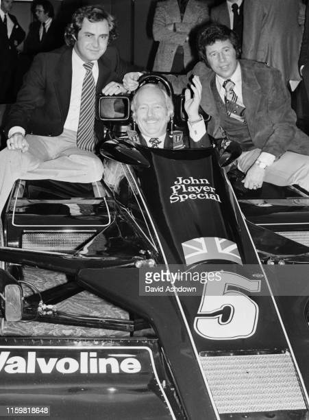 """Colin Chapman, design engineer and team principal of John Player Team Lotus sits aboard the JPS Lotus 78""""tFord Cosworth DFV V8 flanked by his two..."""