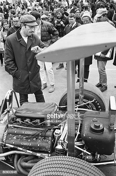 Colin Chapman Lotus designer checks time to start of race next to his LotusFord Type 49B Formula One car in the United States Grand Prix held at...