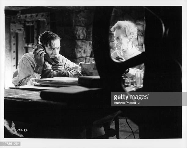 Colin Clive on the phone as Ernest Thesiger looks on in a scene from the film 'Bride Of Frankenstein' 1935