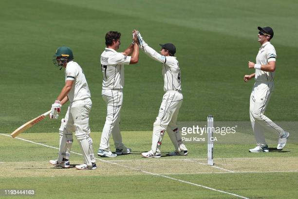 Colin de Grandhomme and BJ Watling celebrate the wicket of Joe Burns of Australia during day one of the First Test match between Australia and New...