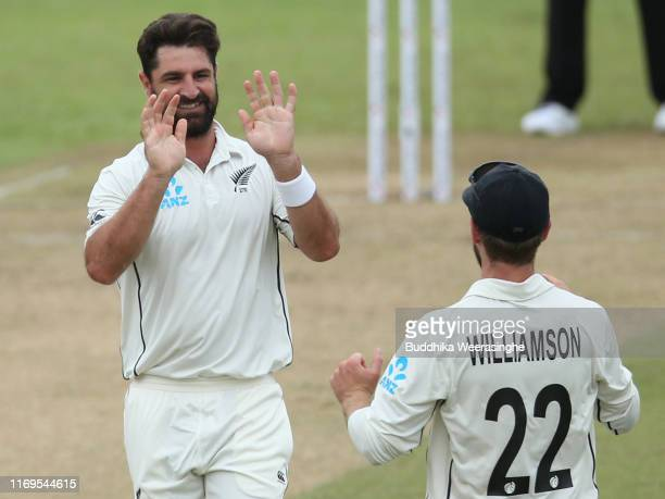 Colin de Grandhomme of New Zealand celebrates with his team caption Kane Williamson after taking the wicket of Kusal Mendis of Sri Lanka during day...
