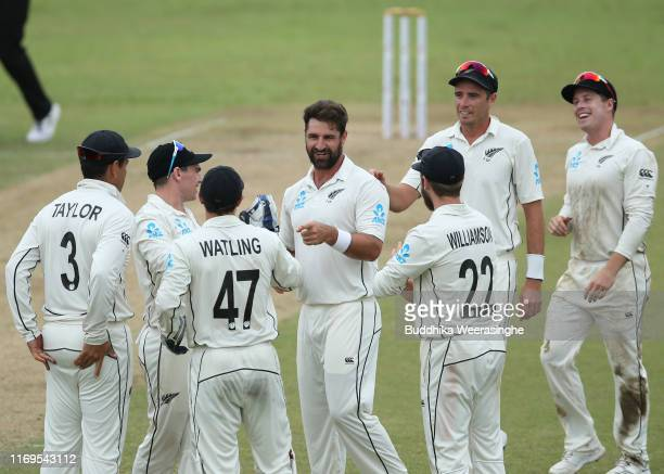 Colin de Grandhomme of New Zealand celebrates with his team mate after taking the wicket of Kusal Mendis of Sri Lanka during day one of the Second...
