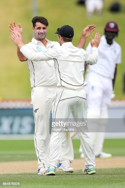 Colin de Grandhomme of New Zealand celebrates with Kane Williamson after taking the wicket of Kemar Roach of the West Indies during day four of the...