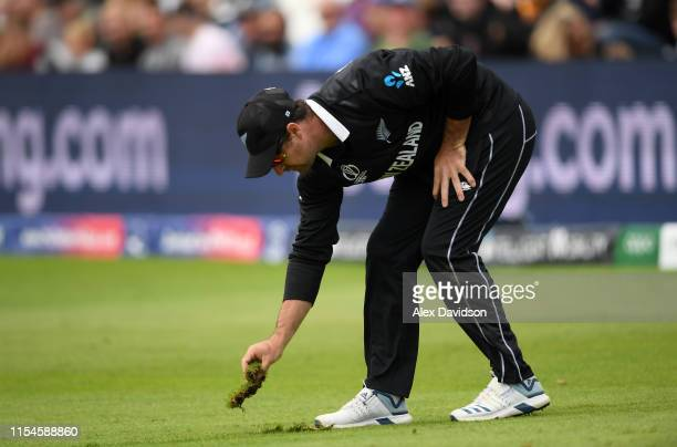 Colin de Grandhomme of New Zealand replaces his divot after dropping Hazratullah Zazai of Afghanistan during the Group Stage match of the ICC Cricket...