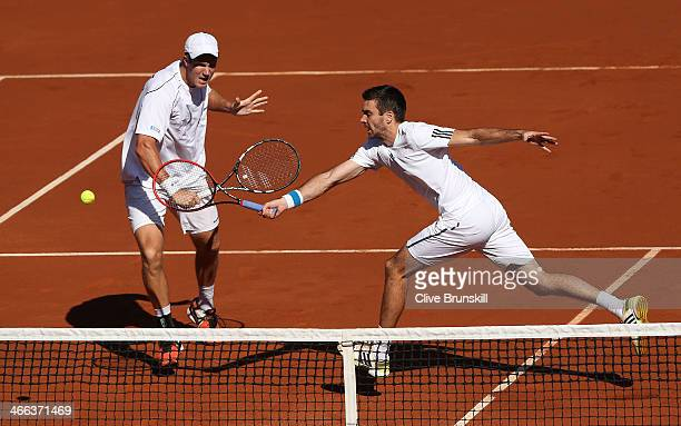 Colin Fleming and Dominic Inglot of Great Britain in action against Bob Bryan and Mike Bryan of the United States in their doubles match during day...