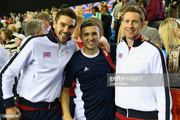 Colin Fleming and Jonathan Marray of Great Britain celebrate with Dan Evans of Great Britain after their teams success over Russia during day three...