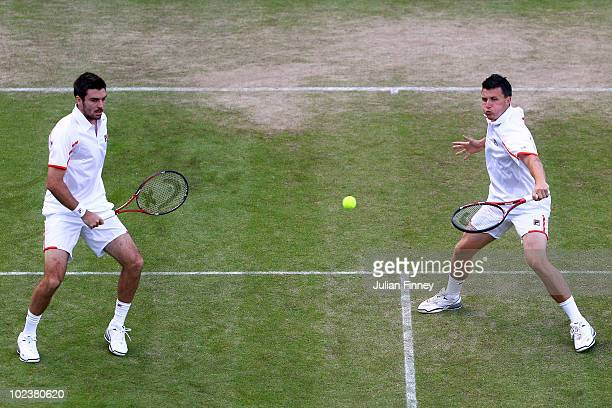 Colin Fleming and Kenneth Skupski of Great Britain in action during their doubles match against Nicolas Mahut and Arnaud Clement of France on Day...