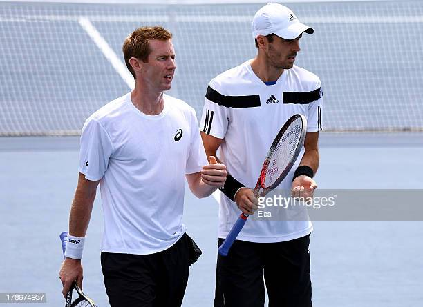 Colin Fleming of Great Britain talks tactics with his partner Jonathan Marray of Great Britain during their men's doubles second round match against...