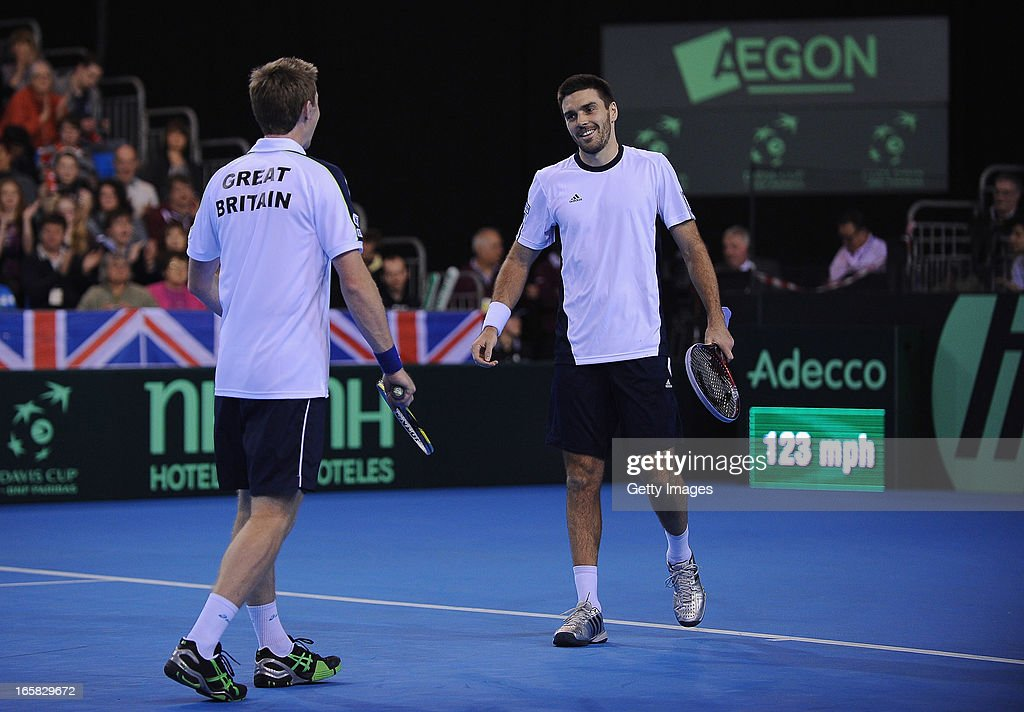 Colin Flemming (R) and Jonny Marray of Great Britain smile after they win a point against Victor Baluda and Igor Kunitsyn of Russia during day two of the Davis Cup match between Great Britain and Russia at Ricoh Arena on April 6, 2013 in Coventry, England.