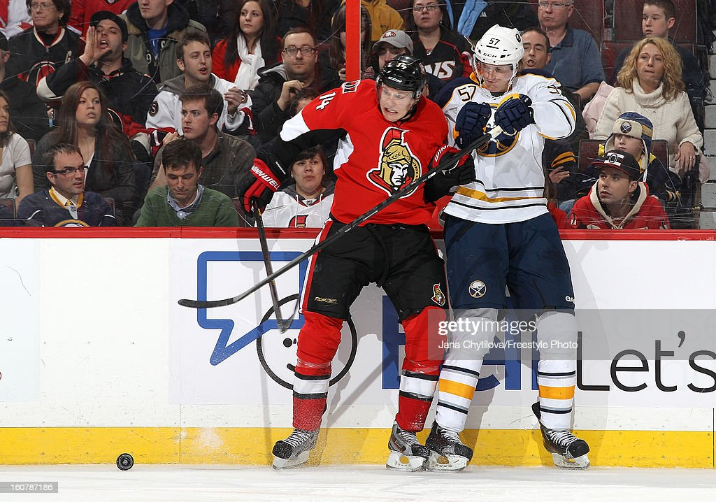 Colin Greening #14 of the Ottawa Senators is checked along the boards by Tyler Myers #57 of the Buffalo Sabres during an NHL game at Scotiabank Place on February 5, 2013 in Ottawa, Ontario, Canada.