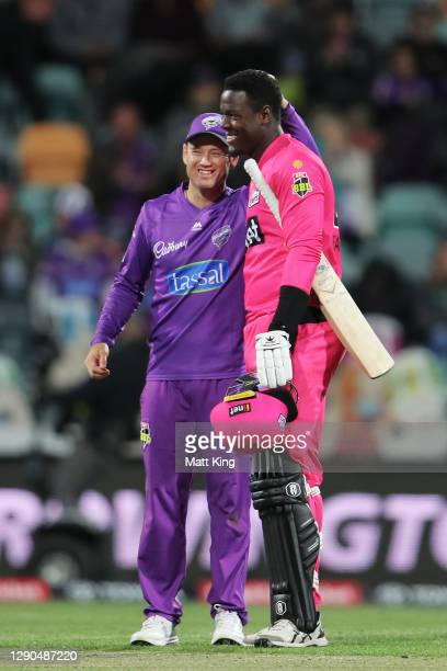 Colin Ingram of the Hurricanes comes together with Carlos Brathwaite of the Sixers after the Big Bash League match between the Hobart Hurricanes and...