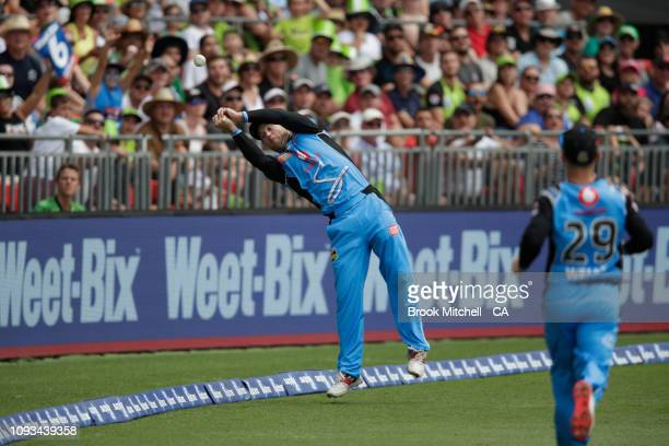 Colin Ingram of the Strikers dives for a catch off Shane Watson of the Thunder during the Big Bash League match between the Sydney Thunder and the...