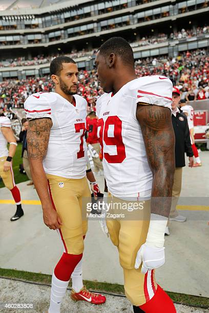 Colin Kaepernick and Aldon Smith of the San Francisco 49ers talk on the sideline prior to the game against the Oakland Raiders at Oco Coliseum on...