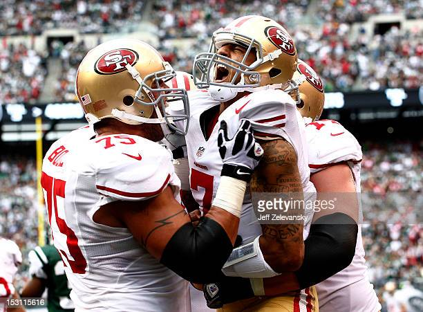 Colin Kaepernick celebrates a touchdown with Alex Boone and Joe Staley of the San Francisco 49ers during a game against the New York Jets at MetLife...