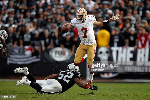 Colin Kaepernick of the San Francisco 49ers avoids the sack from Khalil Mack of the Oakland Raiders in the second quarter at Oco Coliseum on December...