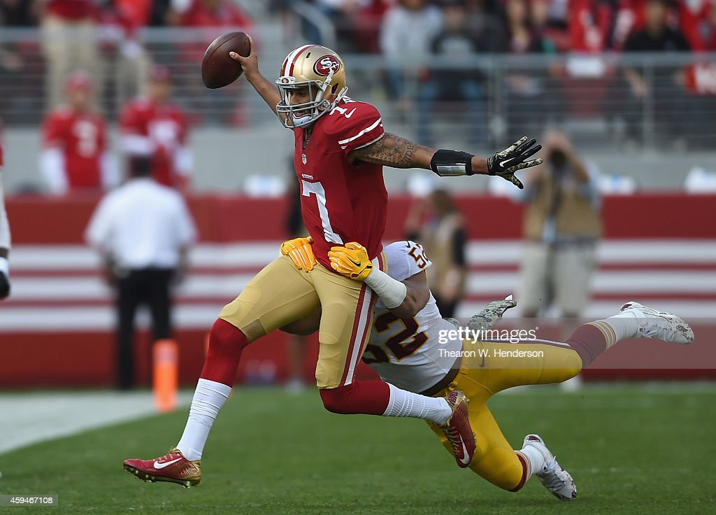 Colin Kaepernick #7 of the San Francisco 49ers fights a tackle from Keenan Robinson #52 of the Washington Redskins at Levi's Stadium on November 23, 2014 in Santa Clara, California.