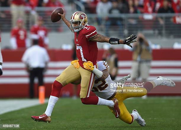 Colin Kaepernick of the San Francisco 49ers fights a tackle from Keenan Robinson of the Washington Redskins at Levi's Stadium on November 23, 2014 in...