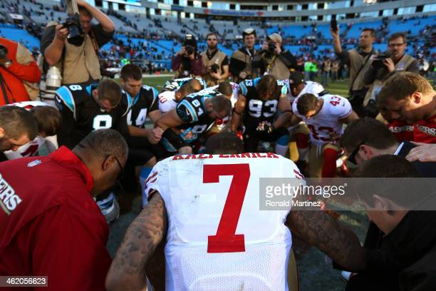 Colin Kaepernick of the San Francisco 49ers kneels with players after defeating the Carolina Panthers during the NFC Divisional Playoff Game at Bank...