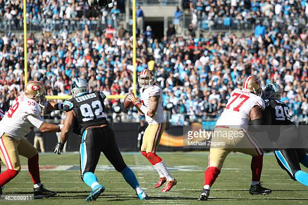 Colin Kaepernick of the San Francisco 49ers looks for a receiver as Jonathan Goodwin and Mike Iupati block during the game against the Carolina...