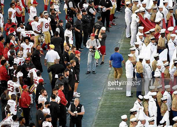 Colin Kaepernick of the San Francisco 49ers on the sidelines as military personel line up before the singing of the National Anthem before a...