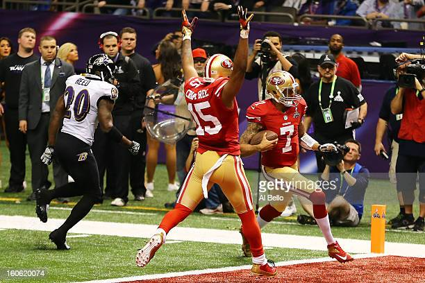 Colin Kaepernick of the San Francisco 49ers runs in for a touchdown in the fourth quarter in front of teammate Michael Crabtree past Ed Reed of the...