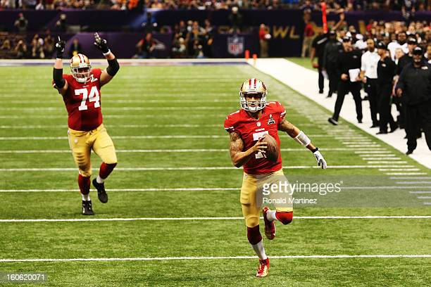 Colin Kaepernick of the San Francisco 49ers runs into the endzone for a 15yard rushing touchdown in the fourth quarter as teammate Joe Staley against...