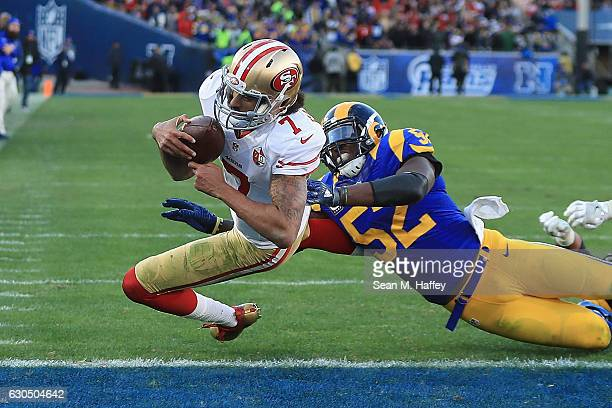 Colin Kaepernick of the San Francisco 49ers rushes for a 13yard touchdown during the fourth quarter as Alec Ogletree of the Los Angeles Rams attempts...